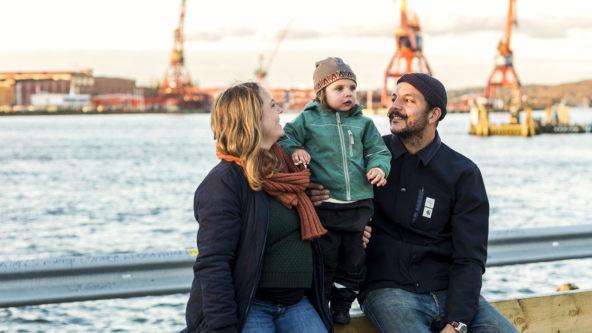En familj med mamma, pappa och ett litet barn sitter vid älvkanten med Lindholmens kranar i bakgrunden.