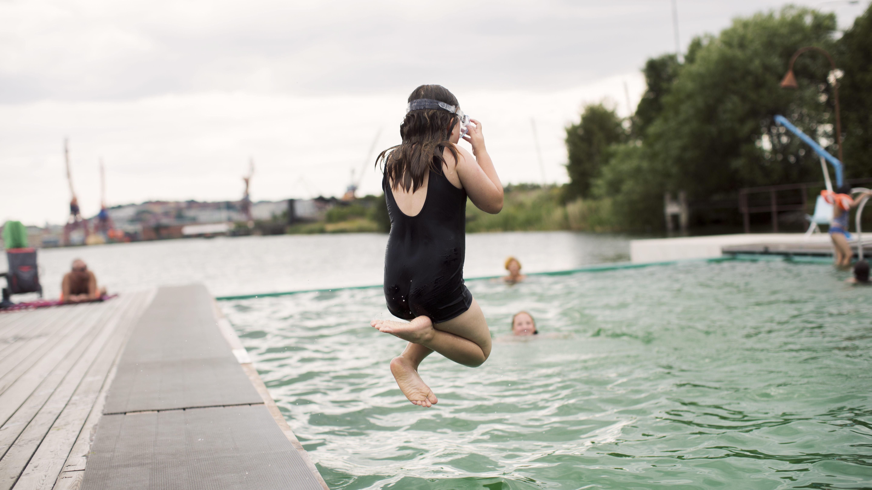 Barn hoppar i bassängen i utebadet Allmänna badet i Jubileumsparken i Frihamnen.