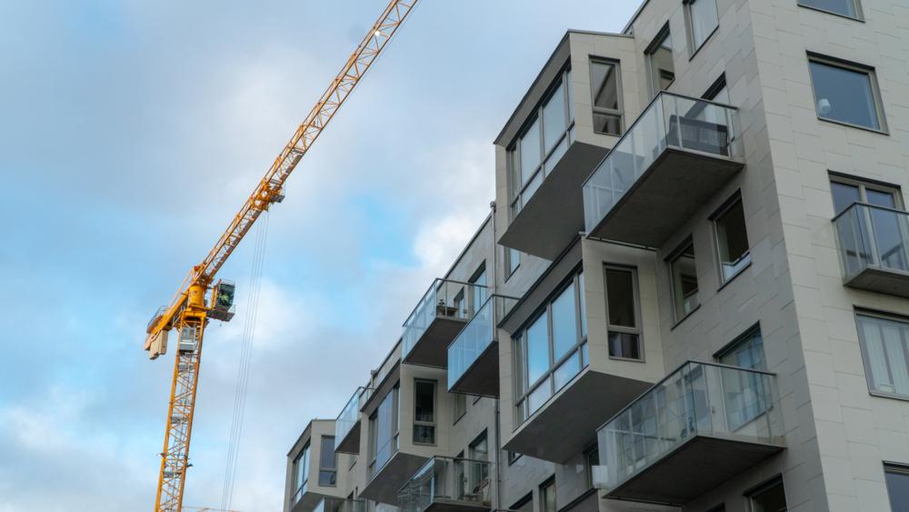 Byggkran vid fastighet i Lindholmshamnen en solig dag.