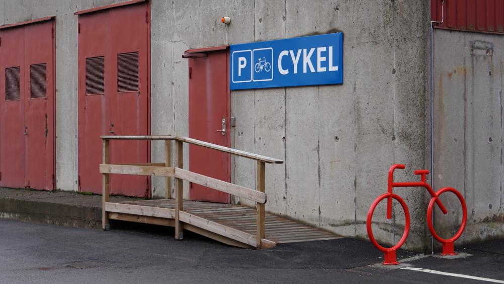 Cykelgarage med en röd cykel utanför.