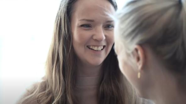 Bild på medarbetaren Evelina på kontoret, leende och pratandes med kollega.