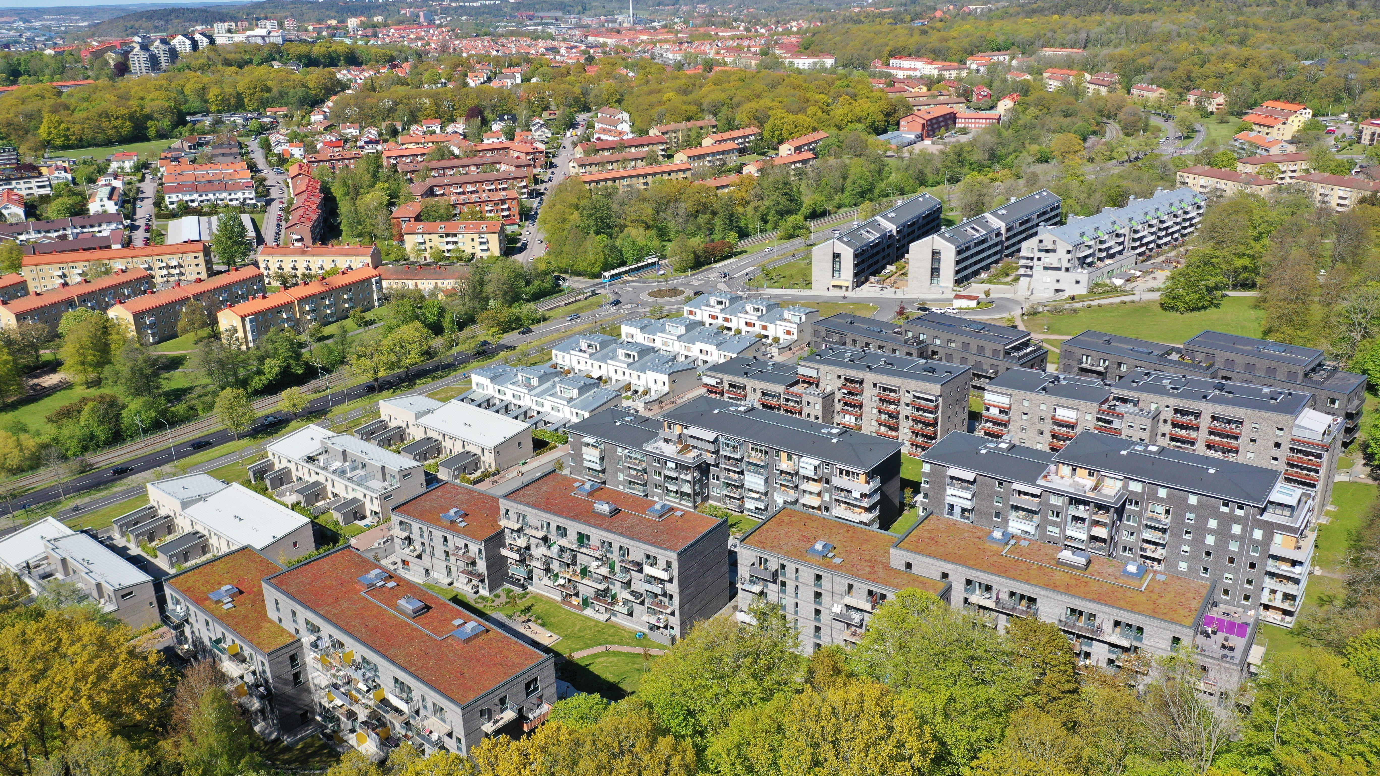 Flygbilder över Örgryte Torp med hyres- och bostadsrättshus i förgrunden och radhus i bakgrunden.