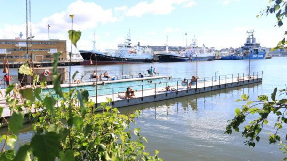 Jubileumsparken och det allmänna badet i Frihamnen en solig sommardag, folk som badar.