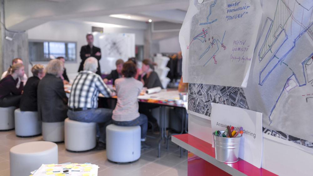 Personer har en dialog runt ett bord fyllt med papper och pennor.