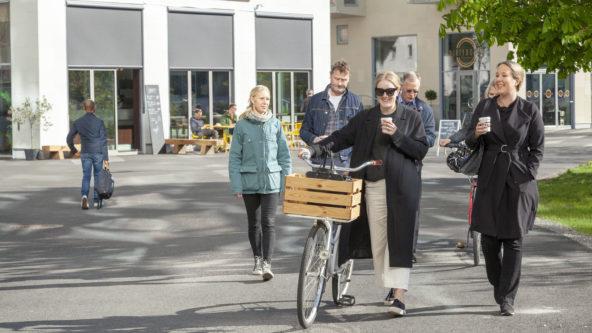 En grupp människor promenerar längs kajen i Lindholmshamnen. I bakgrunden ser vi bostadshus och caféer.