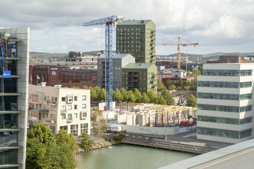 Flygbild över byggnation i Lindholmshamnen, byggkranar och både färdiga samt pågående byggprojekt syns.