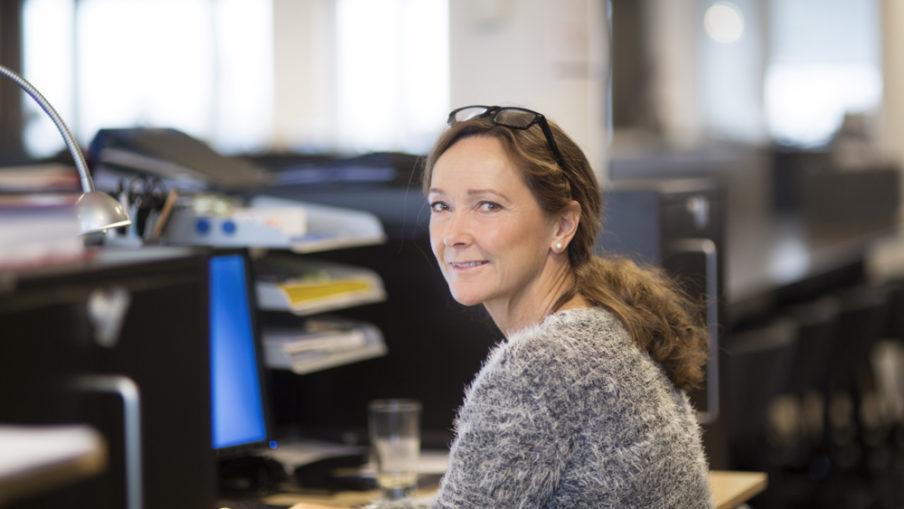 Bild på Elisabeth vid sitt skrivbord på kontoret.