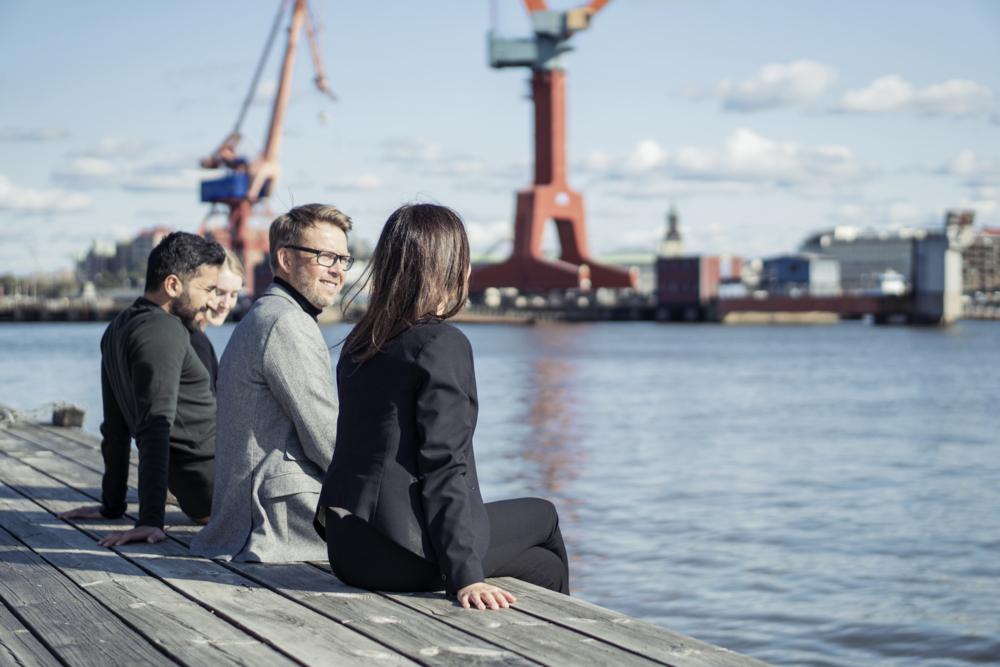 Medarbetare på Älvstranden Utveckling sitter på kajen och tittar ut över kranarna och Göta älv.