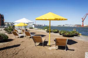 Solstolar, parasoller och konstgjordsandstrand vid Playa Skeppsbron.