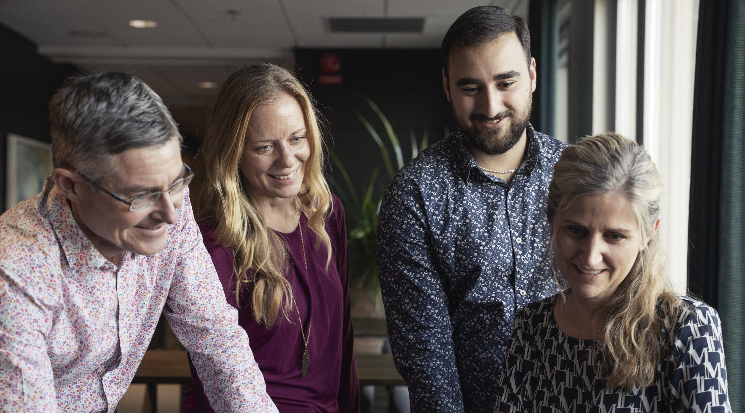 Fyra medarbetare ser på datorskärm.